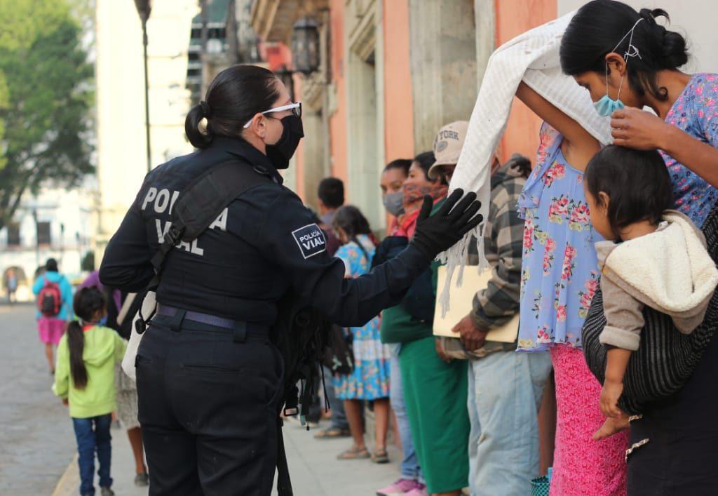 Mujer policía dando indicaciones a gente formada en la fila de acceso al banco